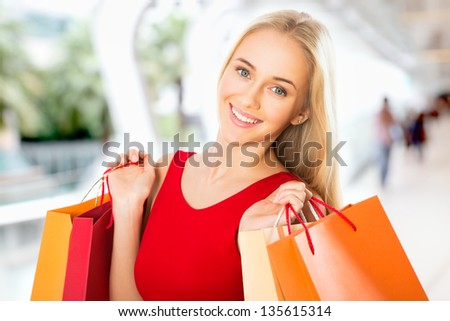 Beautiful young woman with shopping bags in a supermarket - stock photo