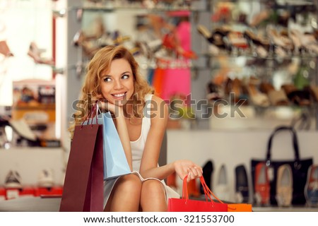 Beautiful young woman with shopping bags in shop - stock photo