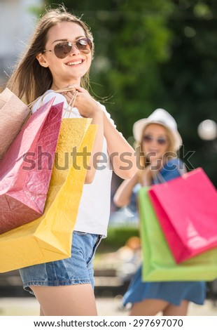 Beautiful young woman with shopping bags looking at camera and smiling while her friend standing on background.