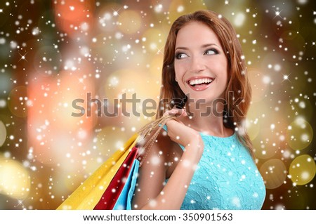 Beautiful young woman with shopping bags on bright background over snow effect