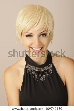 Beautiful young woman with short blond hair looking at camera and smiling