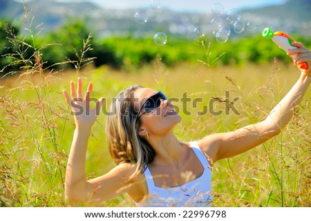 beautiful young woman with soap bubbles on field in summer - stock photo