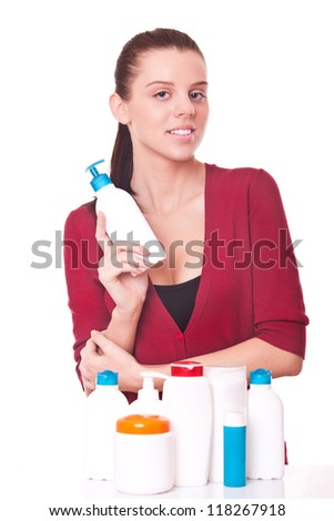 beautiful young woman with spray near many jars for cosmetics and for skincare - stock photo