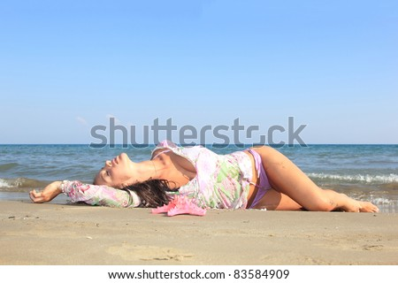 Beautiful young woman with star fish relaxing on the beach in Greece