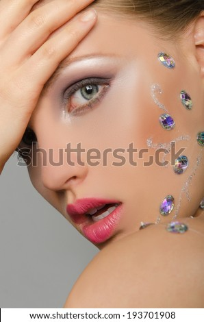 Beautiful young woman with stones on the face on grey background