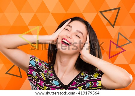 Beautiful young woman, with straight dark hair, wearing on colorful shirt, posing on the orange geometric background with colorful triangles, in studio, waist up - stock photo
