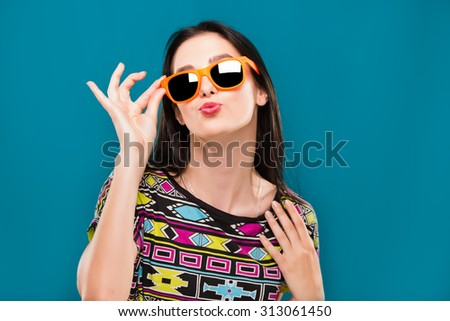 Beautiful young woman, with straight hair, wearing in colorful shirt and orange sunglasses, have fun, on the blue background, in studio, waist up - stock photo