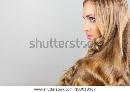 Beautiful young woman with straight long hair on grey background