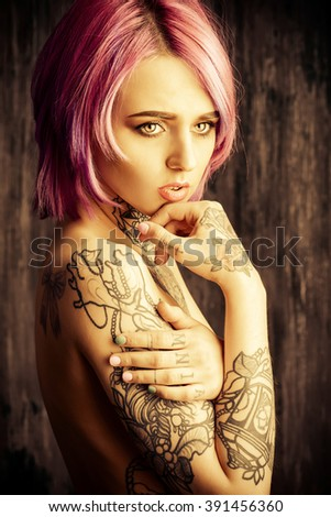 Beautiful young woman with stylish crimson hair and tattoo on her body posing over dark grunge background. Hair coloring. Cosmetics, make-up. Tattoo. - stock photo