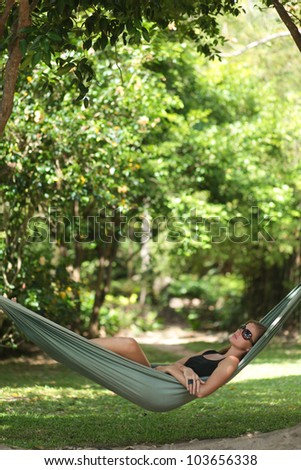 Beautiful young woman with sunglasses resting in a hammock in the shade - stock photo