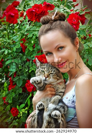 beautiful young woman with tabby cat in the garden with blooming roses - stock photo