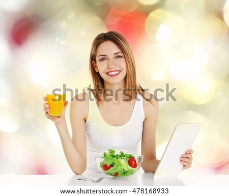 Beautiful young woman with tablet and healthy food on blurred color background. Diet concept.