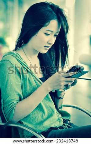 Beautiful young woman with teeth braces using smart phone Vintage Style - stock photo