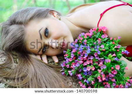 Beautiful young woman with the bouquet of spring flowers
