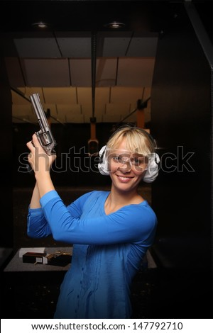 Beautiful young woman with the gun on an indoor shooting range - stock photo