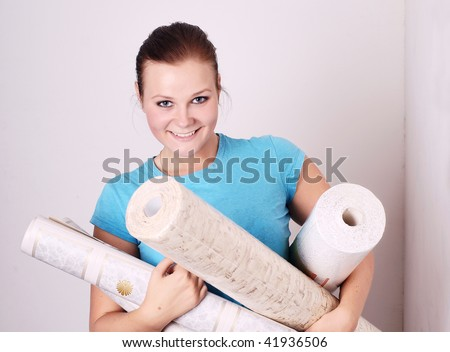 beautiful young woman with the wallpaper in the hands of - stock photo