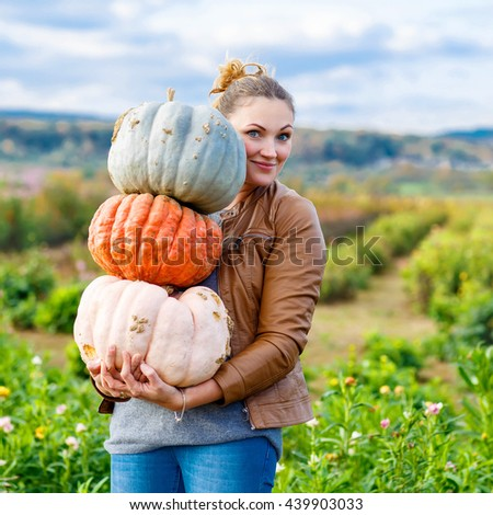 Beautiful young woman with three huge different pumpkins on a farm or patch. Girl having fun with farming. Thanksgiving or halloween.