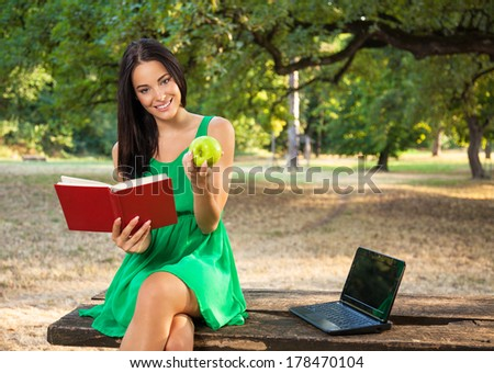 Beautiful young woman with toothy smile holding book and apple in the park and sitting on a wooden table beside laptop.