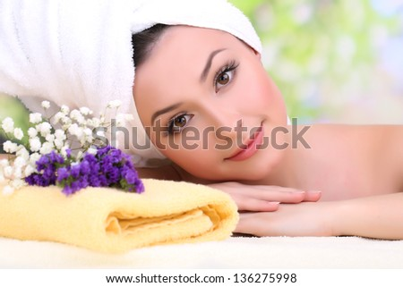 Beautiful young woman with towel on her head on bright background - stock photo