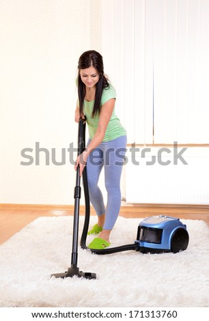 Beautiful young woman with vacuum cleaner in room - stock photo