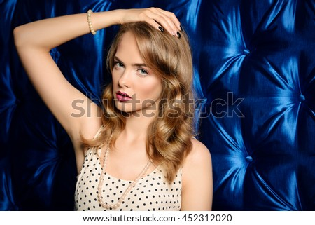 Beautiful young woman with wavy blonde hair posing at studio in light summer dress. Fashion shot. Cosmetics, make-up. - stock photo