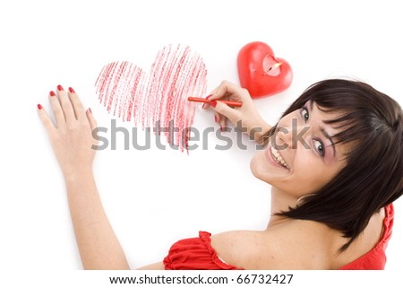 Beautiful young woman with wax crayon lying on floor and drawing heart-shape - stock photo