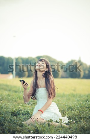beautiful young woman with white dress listening music in the park - stock photo