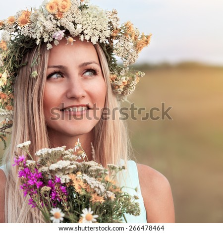 Beautiful young woman with wreath of wildflowers in their hair. Romantic girl with flowers. Summer life. Beauty - stock photo