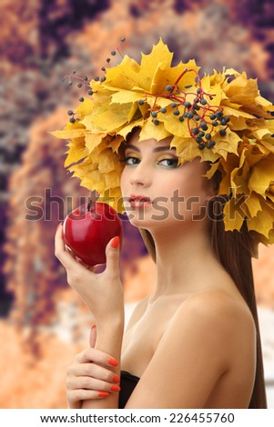 Beautiful young woman with yellow autumn wreath and apple outdoors - stock photo