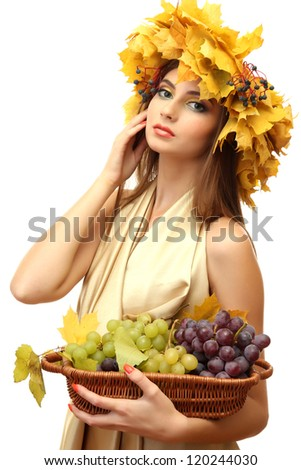 beautiful young woman with yellow autumn wreath and grapes in basket, isolated on white - stock photo