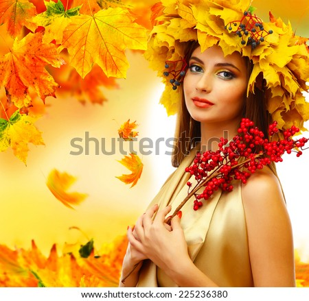 Beautiful young woman with yellow autumn wreath and red berries - stock photo