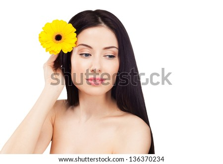 Beautiful young woman with yellow flower. Isolated on white background