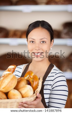 beautiful young woman working in bakery showing basket with bread loafs