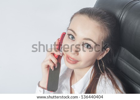 Beautiful young woman working in the room using mobile phone indoors smiling closeup - stock photo
