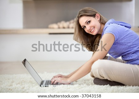 Beautiful young woman working on a laptop indoors
