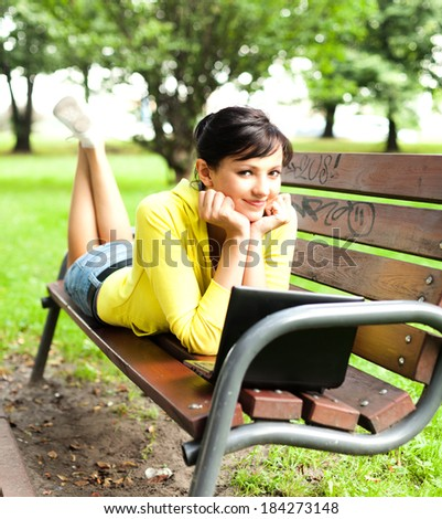 Beautiful young woman working on laptop computer at the park, full lenght - stock photo