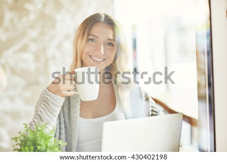 Beautiful young woman working on laptop, holding a cup of drink and looking at camera at the cafe. Freelancer. Through glass