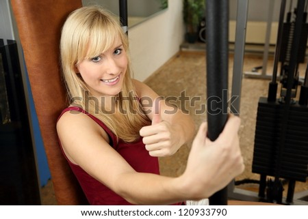 Beautiful young woman working out in a fitness center - stock photo