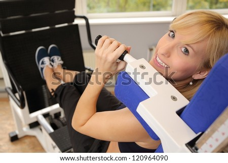 Beautiful young woman working out in a fitness center looking over her shoulder - stock photo