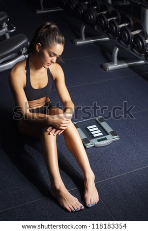 Beautiful young woman working out in fitness club
