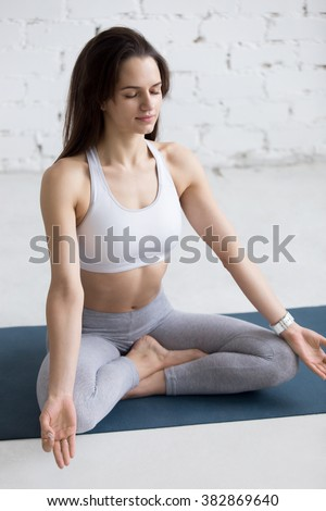 Beautiful young woman working out in loft interior, doing yoga exercise on blue mat, Sitting in Easy (Decent, Pleasant Posture), Sukhasana with closed eyes, meditating, breathing - stock photo