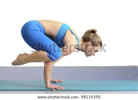 Beautiful young woman working out in the gym. She is in yoga pose standing firmly on her hands. - stock photo
