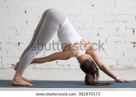 Beautiful young woman working out indoors, doing yoga exercise in the room with white walls, Revolved Downward-Facing Dog Pose, Parivrtta Adho Mukha Svanasana, full length, back view