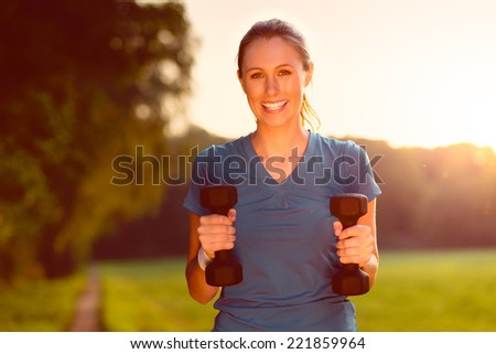 Beautiful young woman working out with dumbbells outdoors in the countryside in evening light looking at the camera with a vivacious smile, health and fitness concept - stock photo