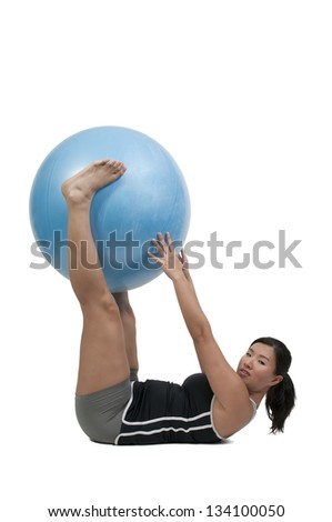 Beautiful young woman working with an aerobic exercise ball