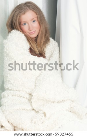 beautiful young woman wrapped in a blanket - stock photo