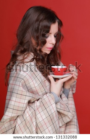 Beautiful young woman wrapped in a blanket and drinking morning coffee