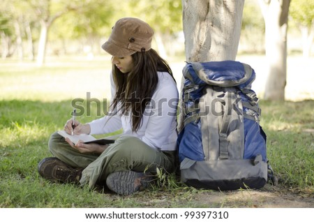 Beautiful young woman writing on a journal about her hiking trip