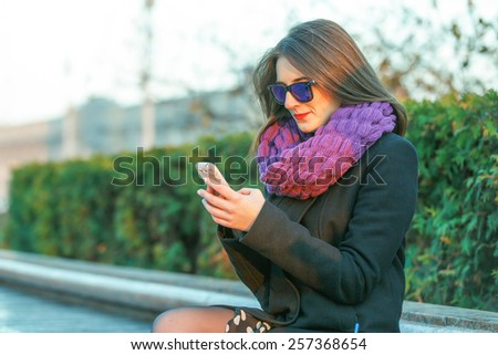 Beautiful young woman writing sms message on the phone in summer evening. - stock photo