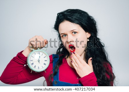 beautiful young woman yawns and stretches after sleeping with an alarm clock, wearing a overalls, close-up isolated on a gray background - stock photo